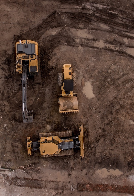 excavator and dozer with steel track tread marks on dirt