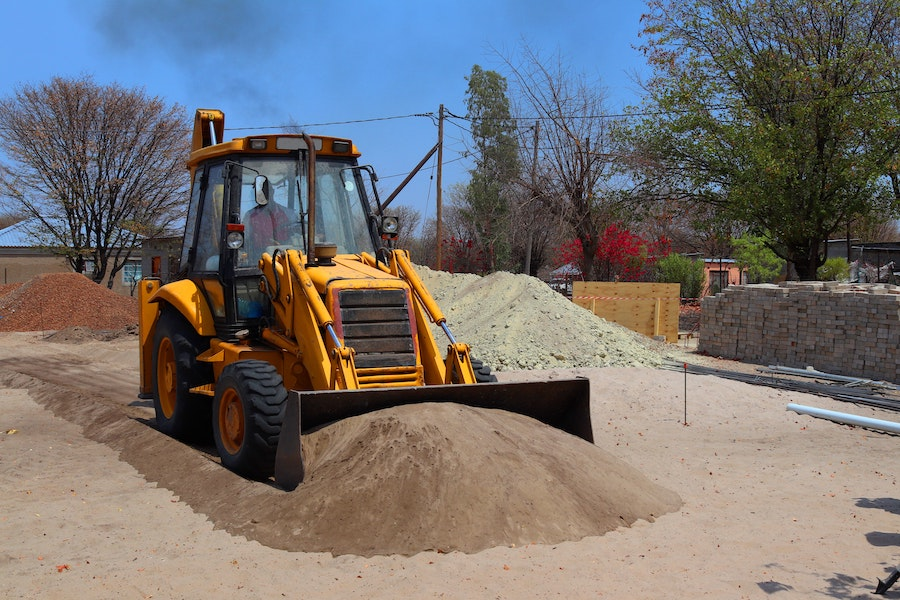 Backhoe loader moving and pushing dirt